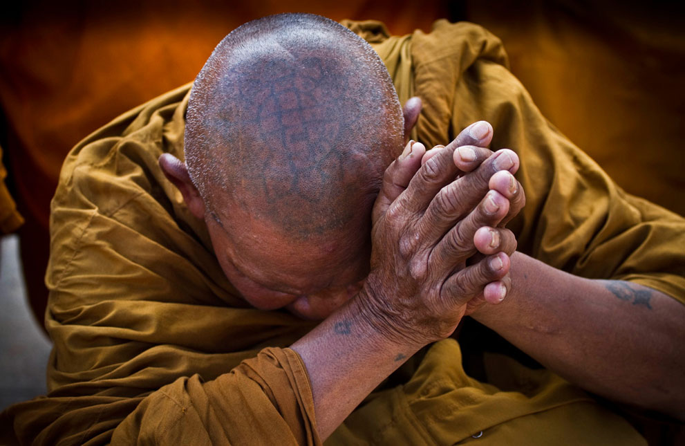 A Thai Buddhist monk, his head tattooed with sacred religious writings, offers prayers to remember those killed in last year's riots in Bangkok, Thailand. (AP Photo/David Longstreath)